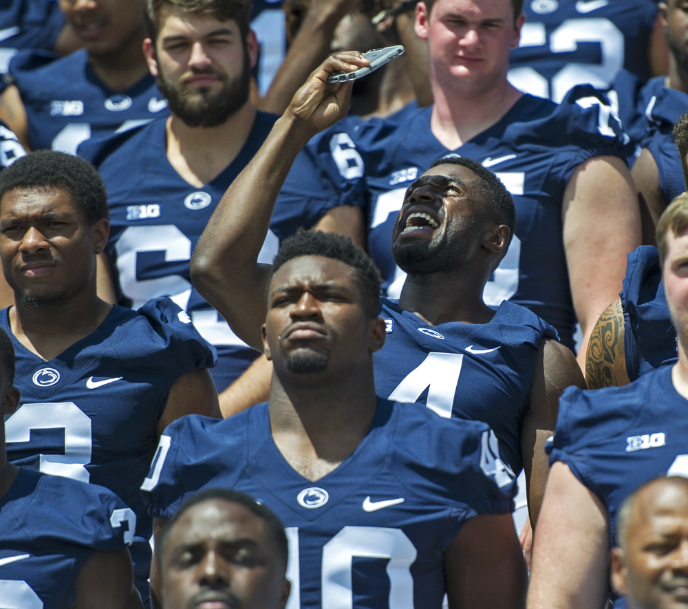 Sophomore center back Nick Scott takes a quick selfie between takes of the team's group photo during photo day at Beaver Stadium on Sunday, Aug. 7, 2016.