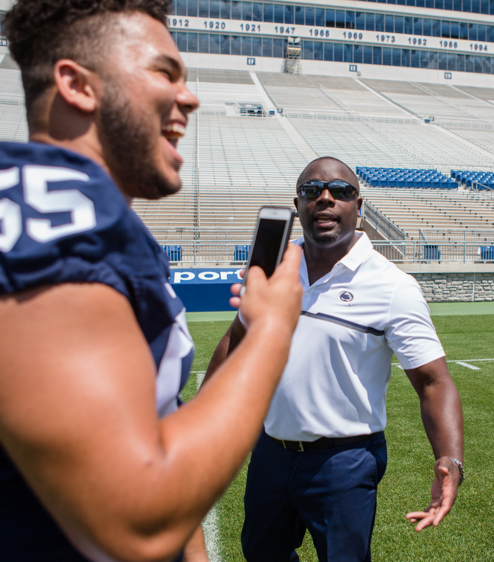 Freshman defensive tackle Antonio Shelton laughs while recording a Snapchat of defensive line coach Sean Spencer during the football team's photo day on the field of Beaver Stadium on Sunday, Aug. 7, 2016.