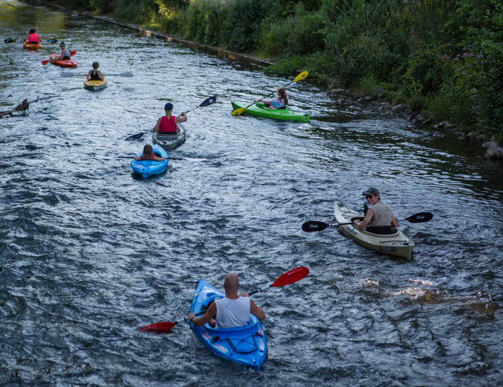 Members of the Rossman and Brown families of Howard paddle their kayaks down Spring Creek after launching from the newly opened waterfront walkway on Sunday, Aug. 7, 2016.