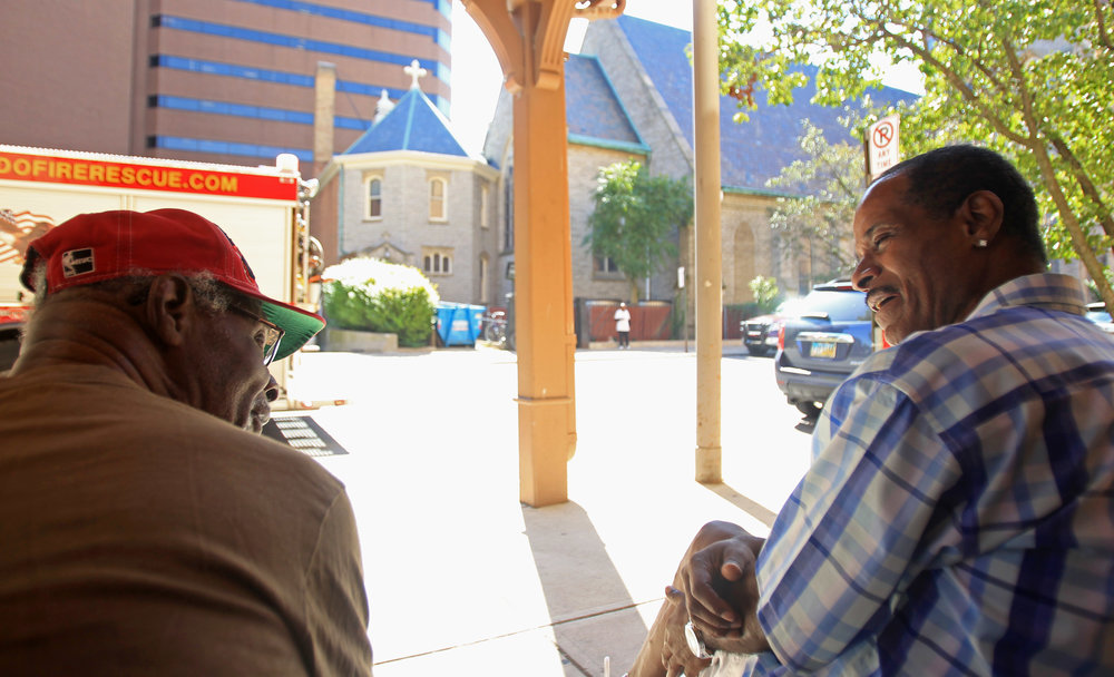 James Moss, left, chats with James Hughes on the sidewalk of St. Clair street in downtown Toledo outside of Renaissance Senior Apartments on Tuesday, Sept. 13, 2016. Moss and Hughes both live at the senior apartments and met at meetings at Trinity Episcopal Church across the street.