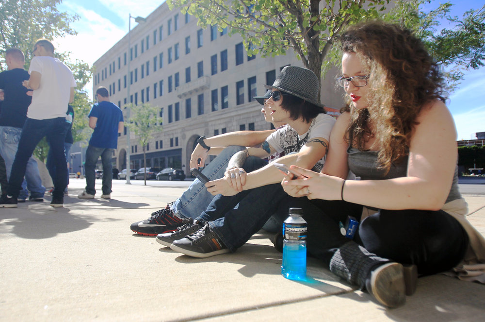 From left to right: Justin Withrow, David Spears, and Katlin Tackett of Dunbar WV. sit on the sidewalk in front of the Huntington Center in Toledo in line for the Avenged Sevenfold concert on Thursday, Sept. 15, 2016.