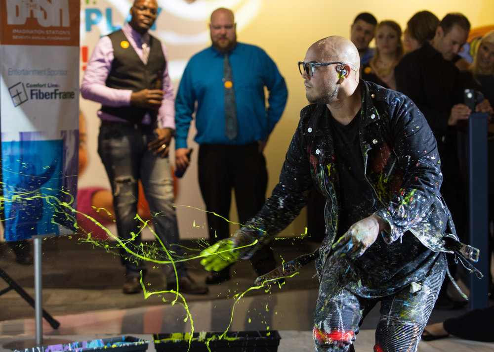 Performance painter David Garibaldi uses his hands to spray one of his paintings with droplets of paint during the Bash 7 fundraiser at Imagination Station in downtown Toledo on Saturday, Sept. 17, 2016.