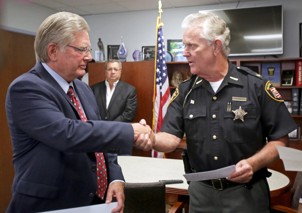Lucas County sheriff John Tharp, right, shakes hands with Louisville Title CEO John Martin after the company presented the sheriff with a $10,000 check to support the operating costs of the Drug Abuse Response Team at the Lucas County Sheriff's Office in downtown Toledo on Tuesday, Sept. 27, 2016.