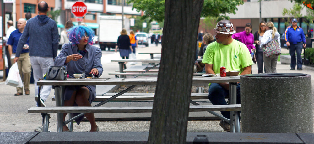 """Local artist Jess """"Cotten Candy"""" Ludwick of Toledo shares a table with Chris Lafaso of Perrysburg during their lunch breaks during Lunch at Levis Square in downtown Toledo on Thursday, Sept. 29, 2016."""
