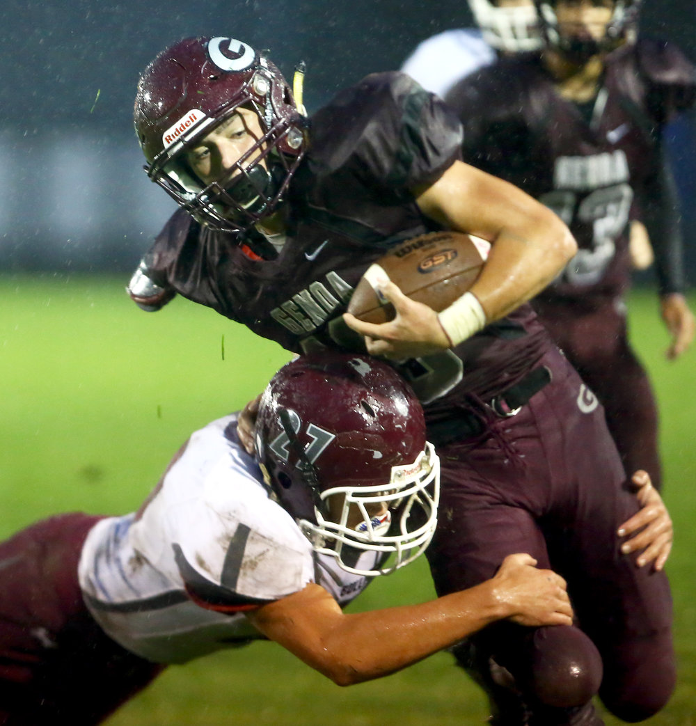 Genoa High School junior running back Josiah Bradfield is tackled by Rossford High School senior defensive back Jacob Perry during the football game at Genoa High School on Friday, Sept. 30, 2016.