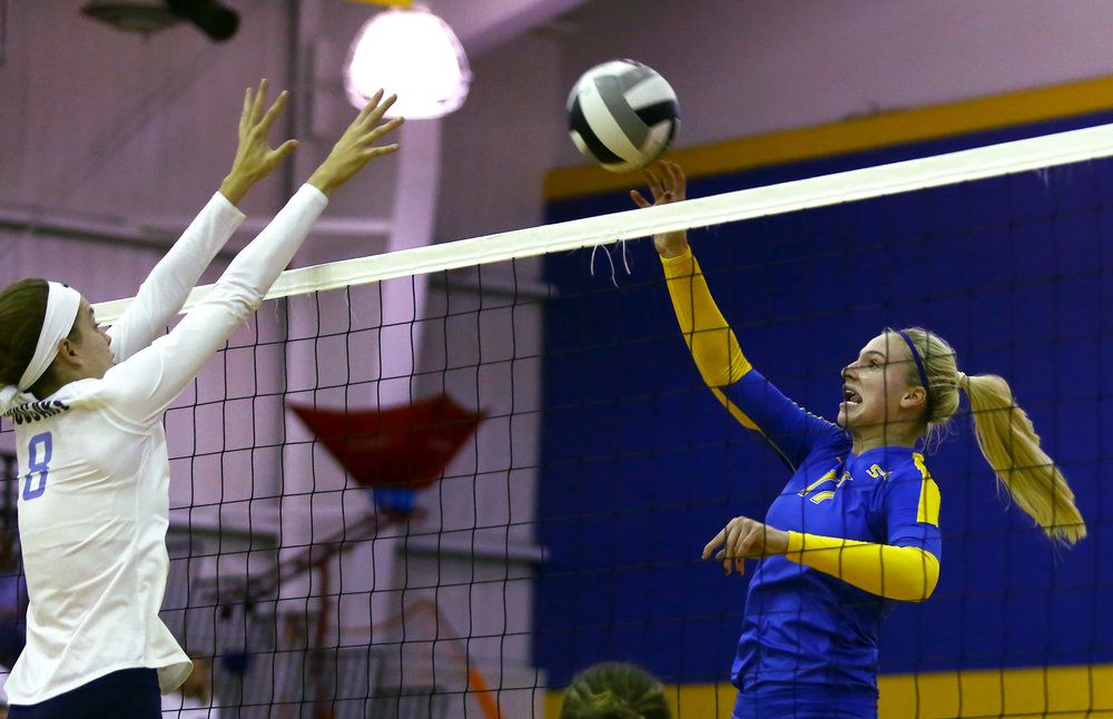 St. Ursula middle hitter Mariah Paulette jumps for a spike as Mount Notre Dame high school middle blocker Sarah Riesenberger attempts to block during the volleyball match at St. Ursula Academy on Saturday, October 1, 2016. St. Ursula won the match 3 sets to 1.