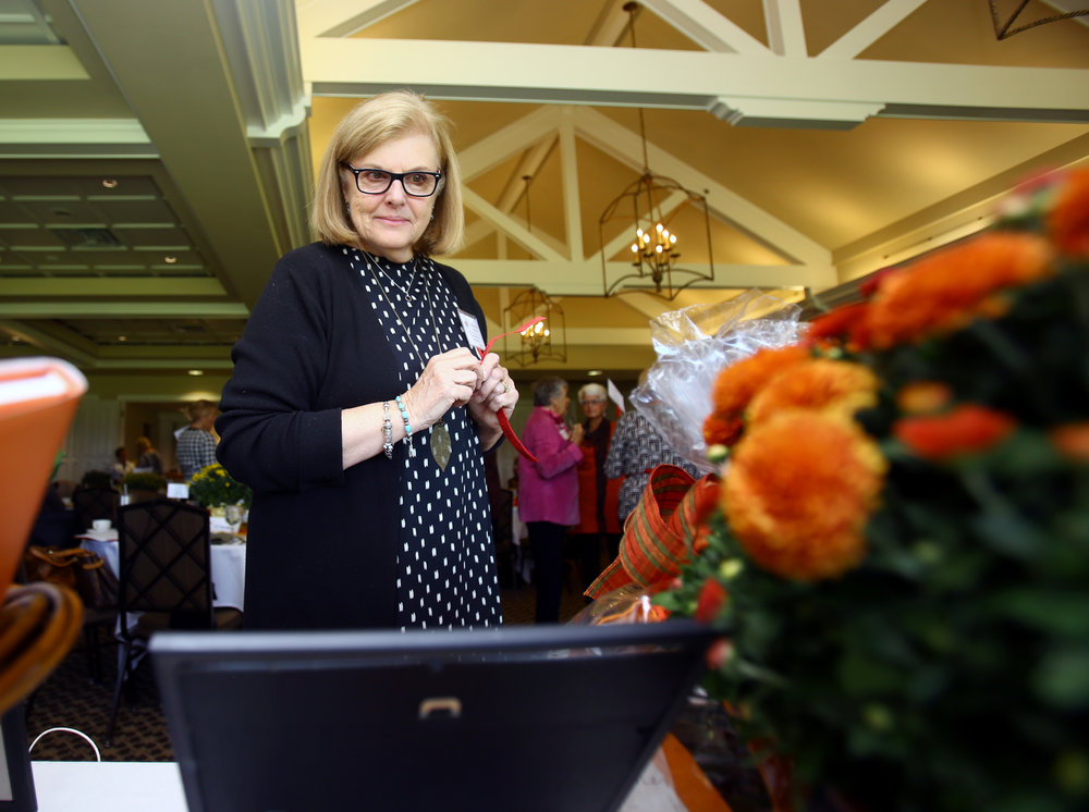 Mary Ellen Bernardo examines the Halloween Ensemble basket available in the silent auction during the Christ Child Society's Red Wagon Shower at the Inverness Club in Toledo on Tuesday, Oct. 4, 2016.