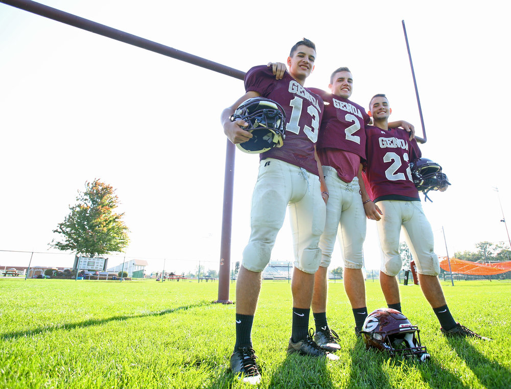 The Bradfield brothers Josiah, left, Matt, center, and Jacob, right, pose for a photograph on the football team's practice field at Genoa Area High School in Genoa on Tuesday, Oct. 4, 2016.