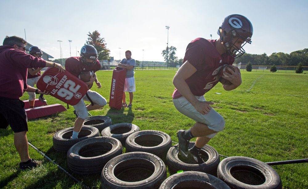 Matt Bradfield runs through agility and ball handling drills during the football team's practice at Genoa Area High School in Genoa on Tuesday, Oct. 4, 2016.