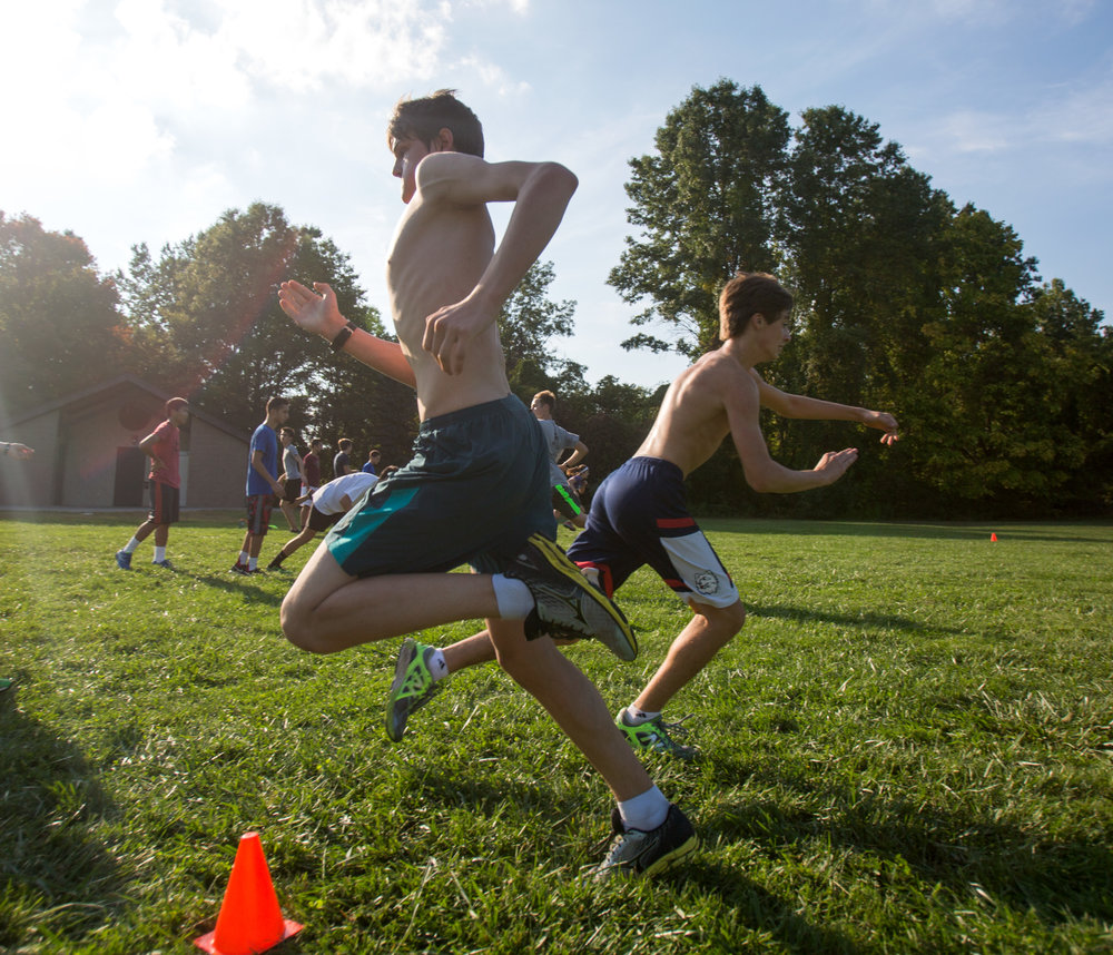 Nicholas Sliter, front, tags off with Ethan Krupp for team ladder sprints during the Ottawa Hill High School cross country practice in Wildwood Preserve Metropark on Thursday, Oct. 6, 2016.