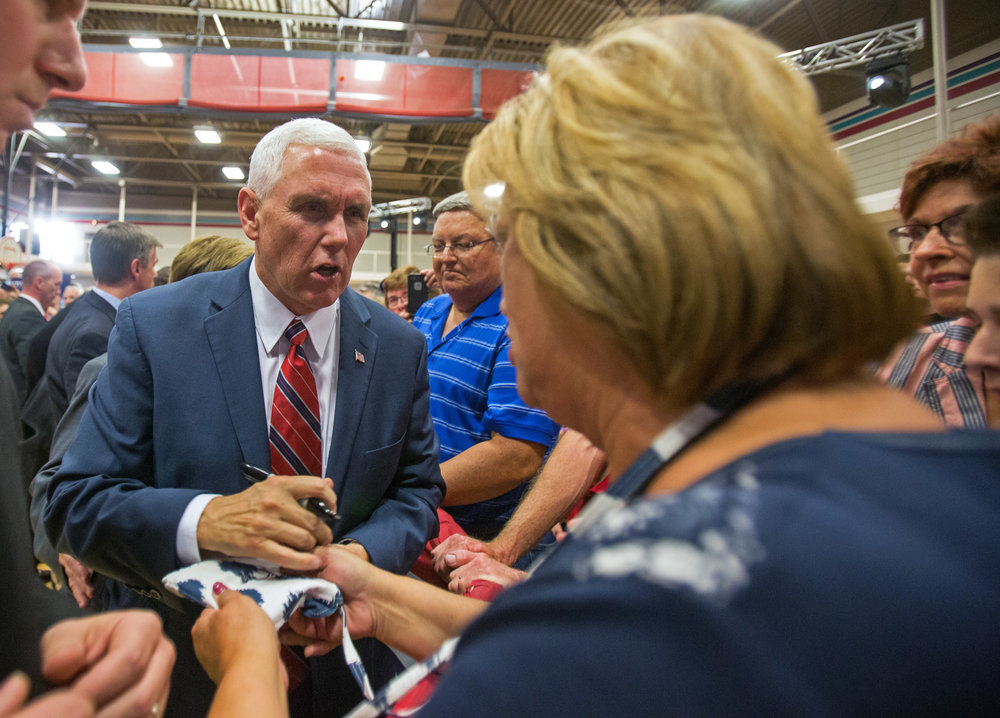 Republican vice presidential candidate Mike Pence signs a supporter's purse after his appearance at the the Rossford Recreation Center on Friday, Oct. 7, 2016.