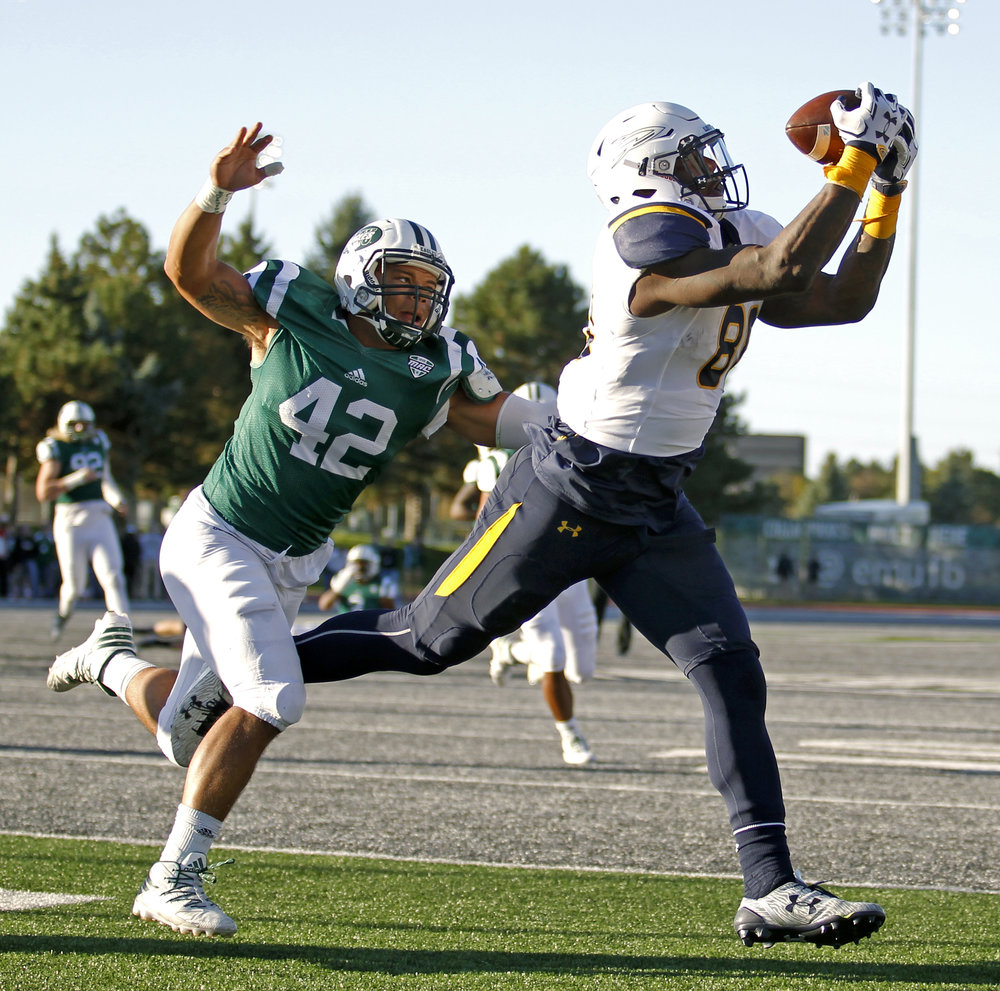 University of Toledo senior tight end Michael Roberts completes a pass for a touchdown while under coverage from Eastern Michigan linebacker Derric Williams during the football game at Rynearson Stadium in Ypsilanti on Saturday, Oct. 8, 2016. Toledo won the game 35-20.