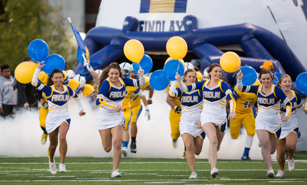 The Findley High School cheer leaders lead the football team out on to the field before the first half of the football game against Central Catholic High School at Donnell Stadium in Findley, Ohio on Friday, Oct. 14, 2016. Central Catholic High School leads the game 21-0 at the half.