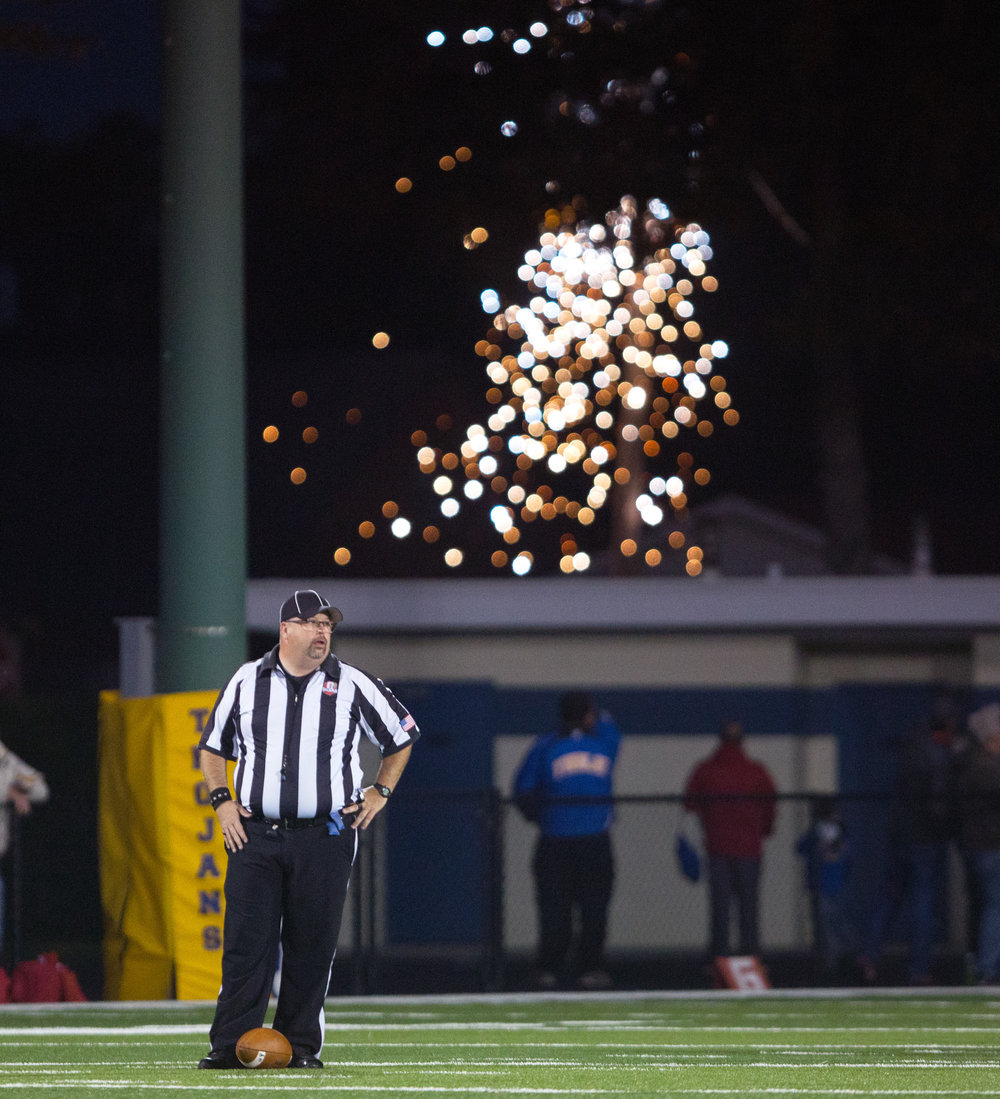 A referee stands by the ball as a power line catches fire cutting power to the scoreboard  at Donnell Stadium in Findley, Ohio during the football game against Central Catholic and Findley High School on Friday, Oct. 14, 2016.