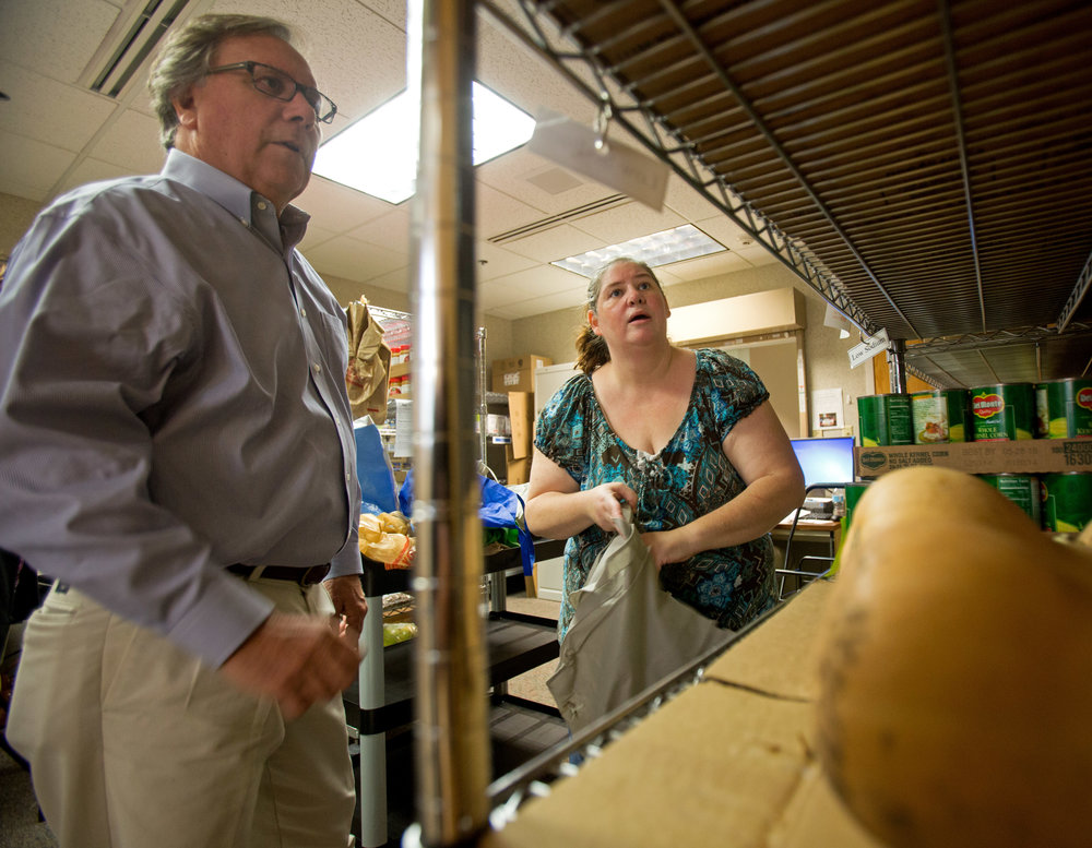 ProMedica Heart Institute cardiologist Dr. Jim Bingle helps Kim Maher of Toledo pick from different vegetable options at the food pharmacy in the ProMedia Center for Health Services on Central Ave. in Toledo on Wednesday, Oct. 19, 2016.
