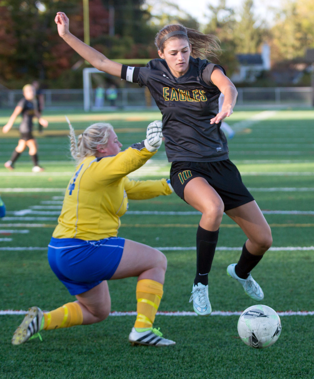 Karleigh Clere of Clay High School jumps passed St. Ursula's goal keeper Caelan Warneke during the Division I girls soccer district tournament at Northview High School Monday, Oct. 24, 2016.