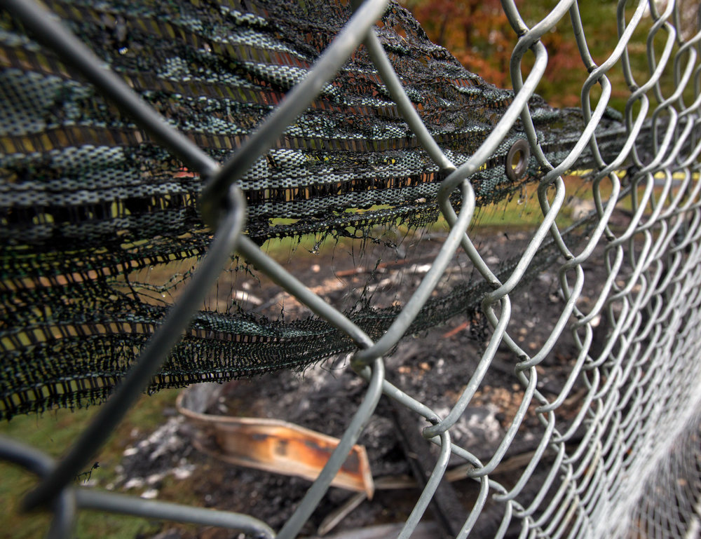 The melted backstop netting and charred remains of a storage shed holding baseball equipment behind Bedford Middle School in Temperance, Mi. that burned down early Wednesday morning photographed on Wednesday, Oct. 26, 2016.