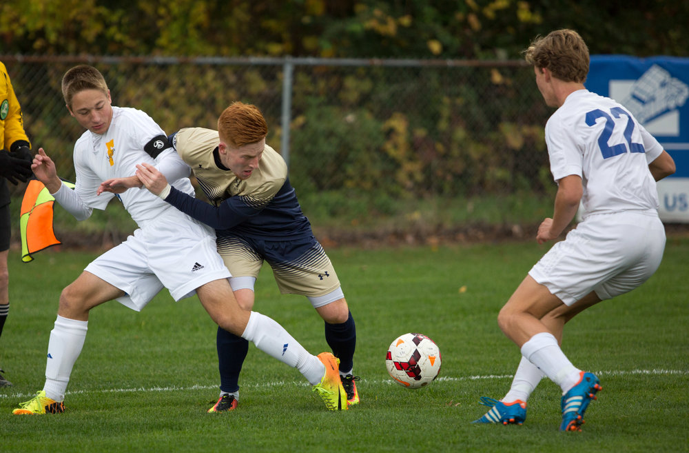 St. John's forward Zachary Buescher fights for control of the ball with Findlay High School midfielder Todd Federici (8) and defender Calvin Meyer (22) during the Div. 1 Boys soccer semifinal game at Southview High School on Wednesday, Oct. 26, 2016.