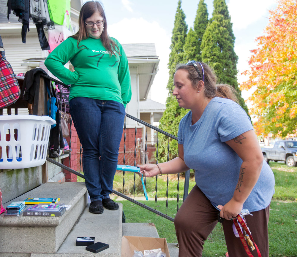 Theresa Szilagye, left, hosts a porch sale on the steps of her home on South Ave. in Toledo as Kristina Benner of Toledo looks through the different phone cases for sale on Thursday, Nov. 3, 2016.
