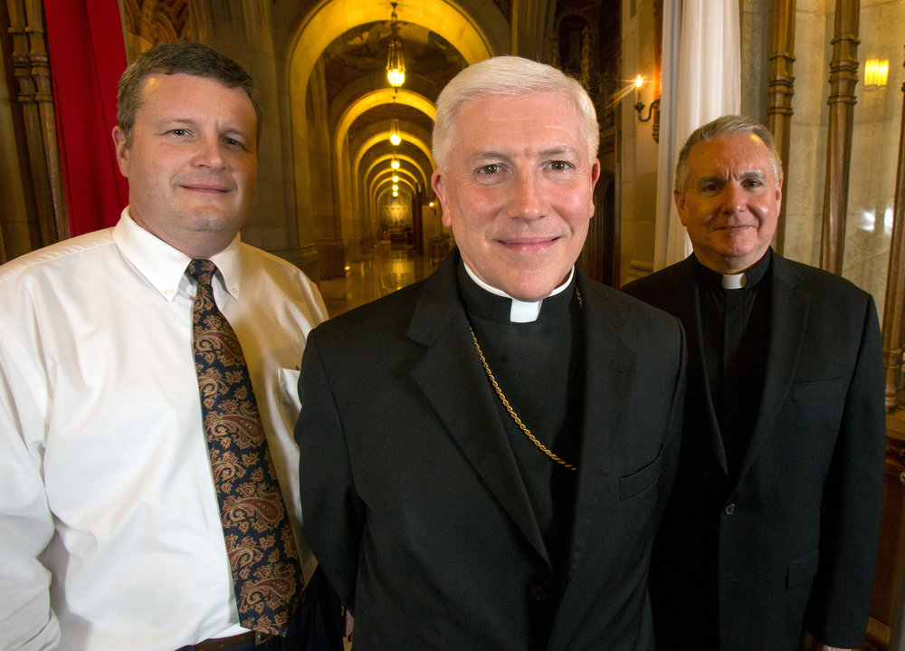 Director of Catechetical Formation David McCutchen, left, Bishop of the Diocese of Toledo Daniel Thomas, center, and Monsignor William Kubacki pose for a photograph at the holy door in the Rosary Cathedral in Toledo on Monday, Nov. 7, 2016.