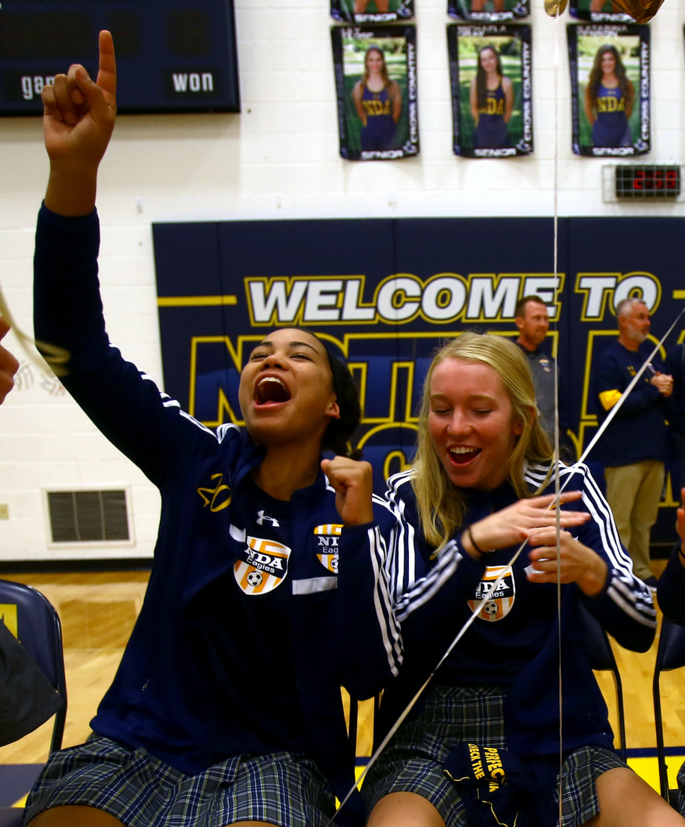 Junior defender Lexa Bauer, left, and senior forward Grace Petrie cheer during a pep rally held in Notre Dame Academy's gym in Toledo for the varsity soccer team before they head to the OSHAA state semi-final game in Sandusky on Monday, Nov. 7, 2016.