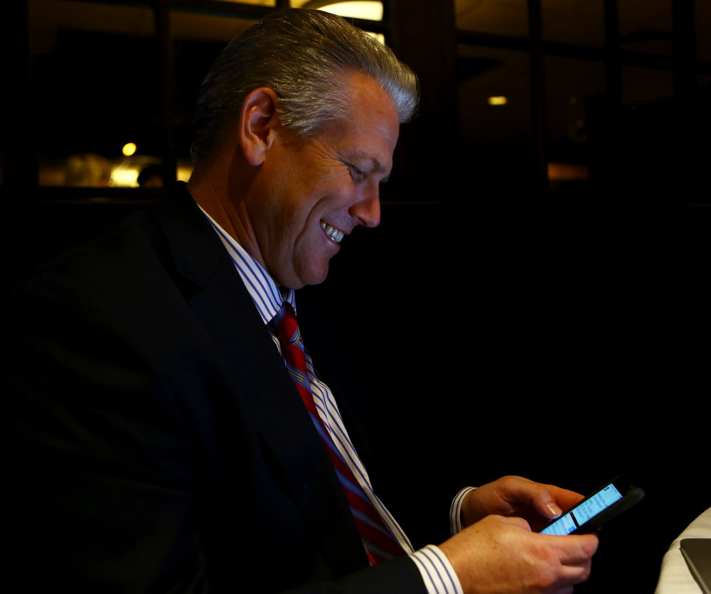 Perrysburg school district superintendent Tom Hosler smiles as he tweets out the passing results of the Perrysburg school renewal operating levy at the Holiday Inn French Quarter in Peerysburg on Tuesday, Nov. 8, 2016.