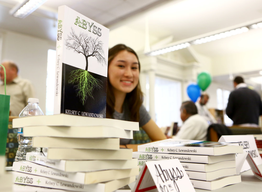 Anthony Wayne High School student Kelsey Lewandowski of Monclova sits at a table during a local authors meet and greet at the Way Public Library in Perrysburg, Oh. with her published books on Sunday Nov. 13, 2016.
