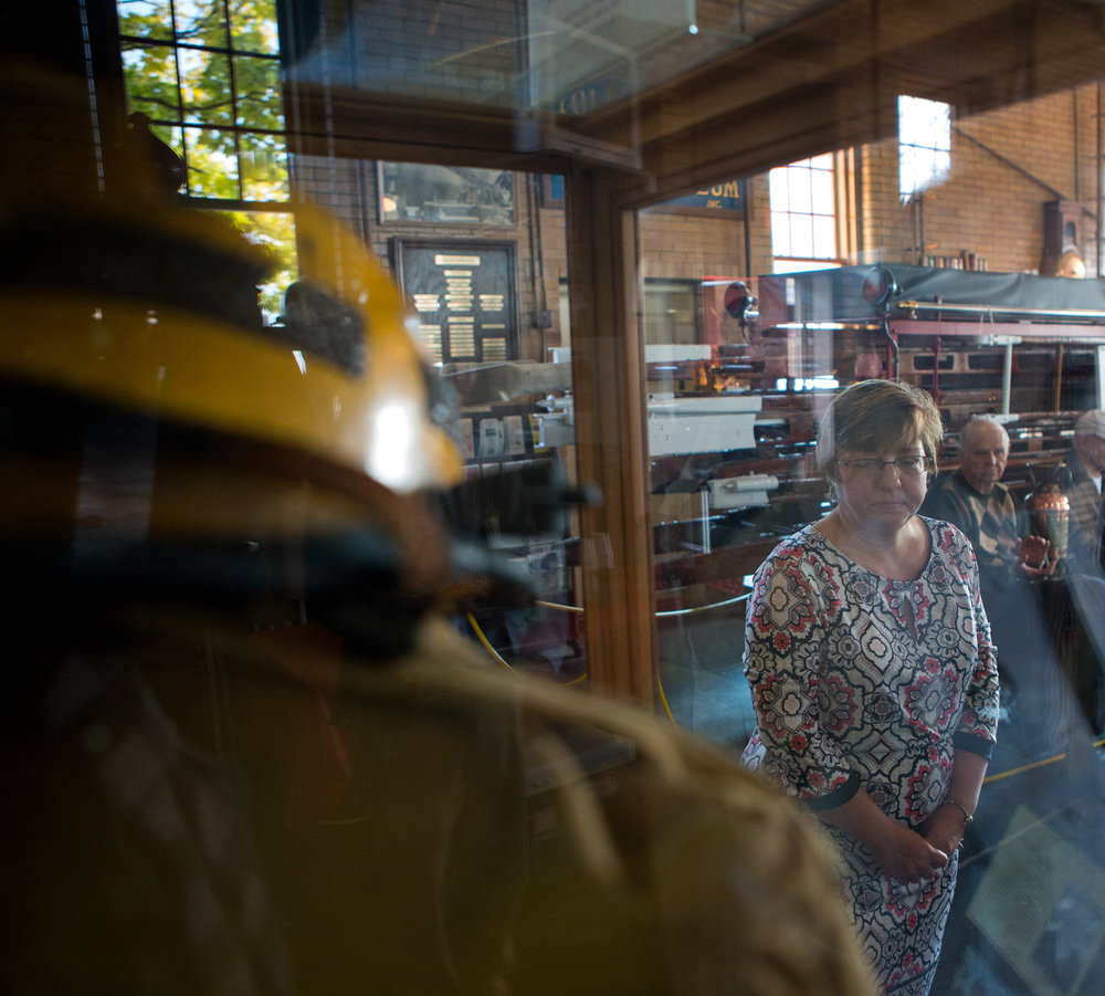 Rhonda Charles of Sylvania stands in front of the display case containing a jacket as well as a charred helmet worn by her brother Henry Plowman while responding to fires at the Pentagon in Washington D.C. after the Sept. 11, 2001 attacks during a dedication ceremony at the Toledo Firefighters Museum on Tuesday, Nov. 15, 2016.
