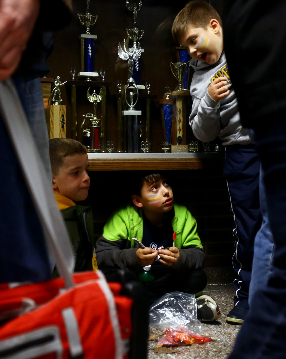 Ryne Maag, left, Andrew Eschbach, center, and Brady Thomas, right, sit by the trophy case in Napoleon High School as they take shelter from the high winds and rain delaying the the OSHAA Div. VI final football game between Patrick Henry High School and Ayersville High School in Napoleon, Oh. High School on Friday, Nov. 18, 2016.