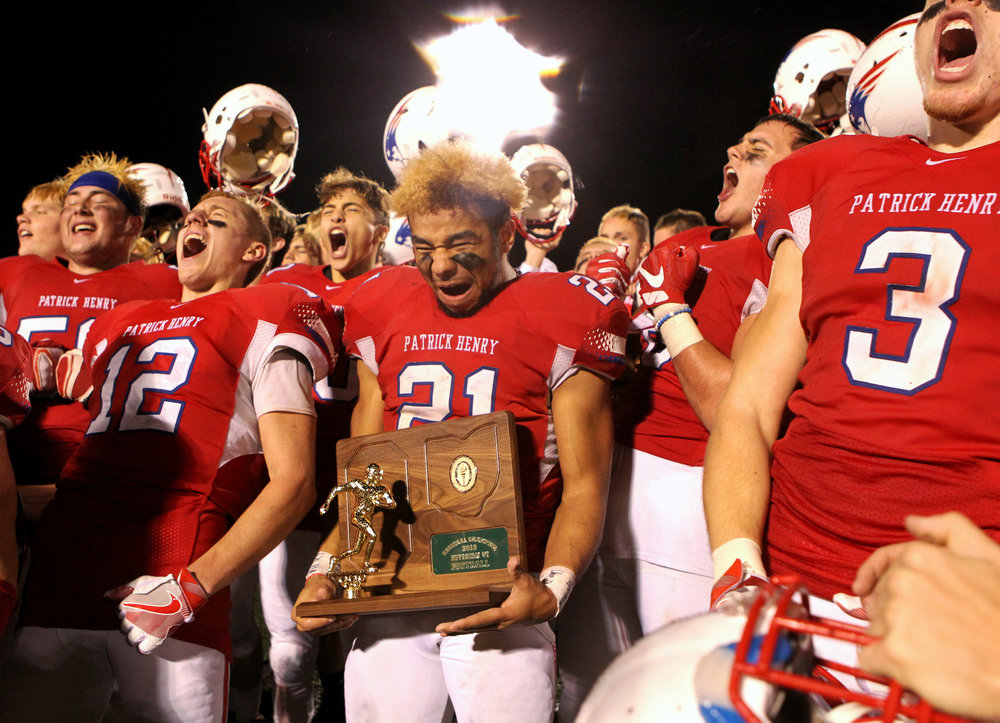 Patrick Henry High School running back Donny Johnson (21) holds the OSHAA Div. VI championship trophy as the team celebrates their 21-19 victory over Ayerville High School at Napoleon High School in Napoleon, Oh. High School on Friday, Nov. 18, 2016.