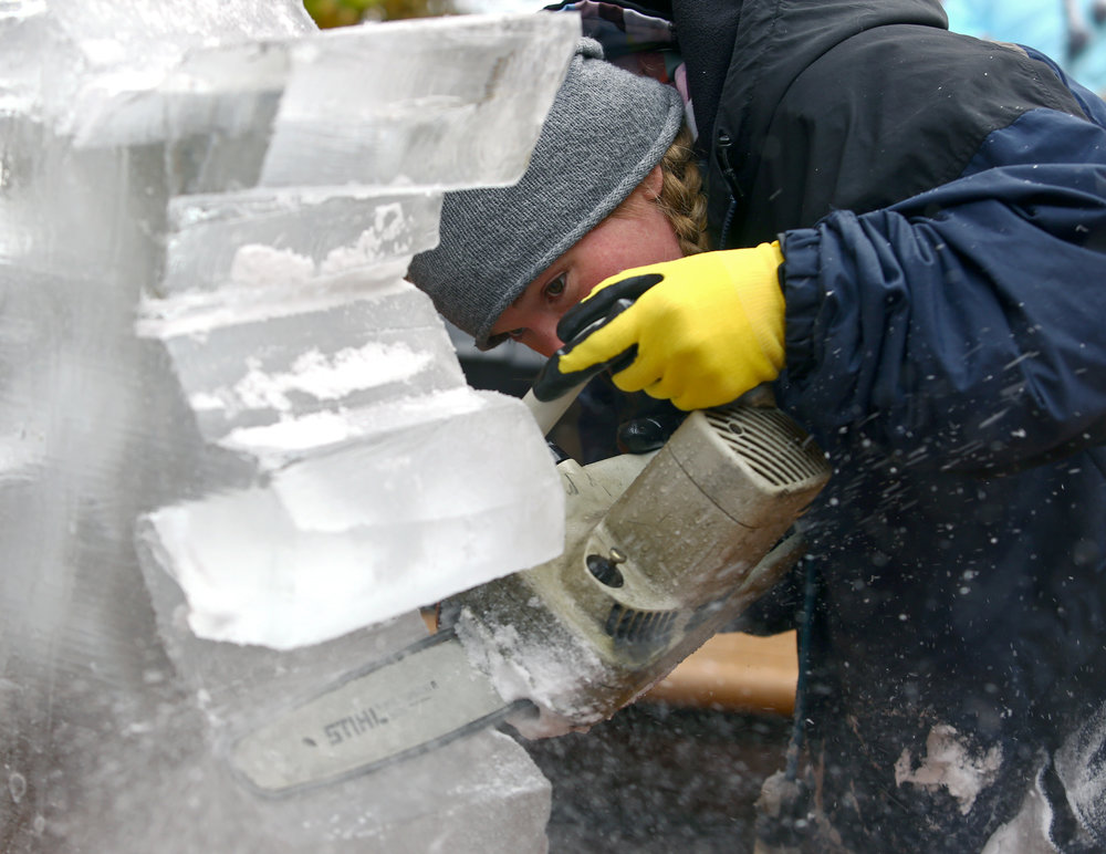 Ice Creations sculptor Stephanie Hugel of Napoleon works on an ice sculpture of a snowflake during the Christmas Open House in downtown Grand Rapids, Oh. on Saturday, Nov 19, 2016.