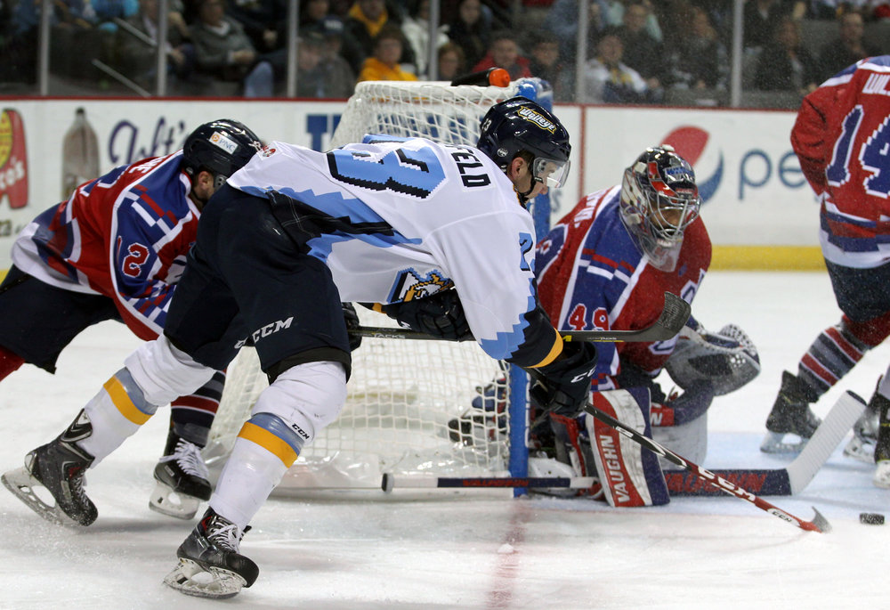 Toledo Walleye forward Alden Hirschfeld (23) hooks the puck around Kalamazoo Wings goalie Joel Martin (49) during the hockey game at the Huntington Center in downtown Toledo, Oh. on Saturday, Nov. 19, 2016. The Walleye won the game 6-2.