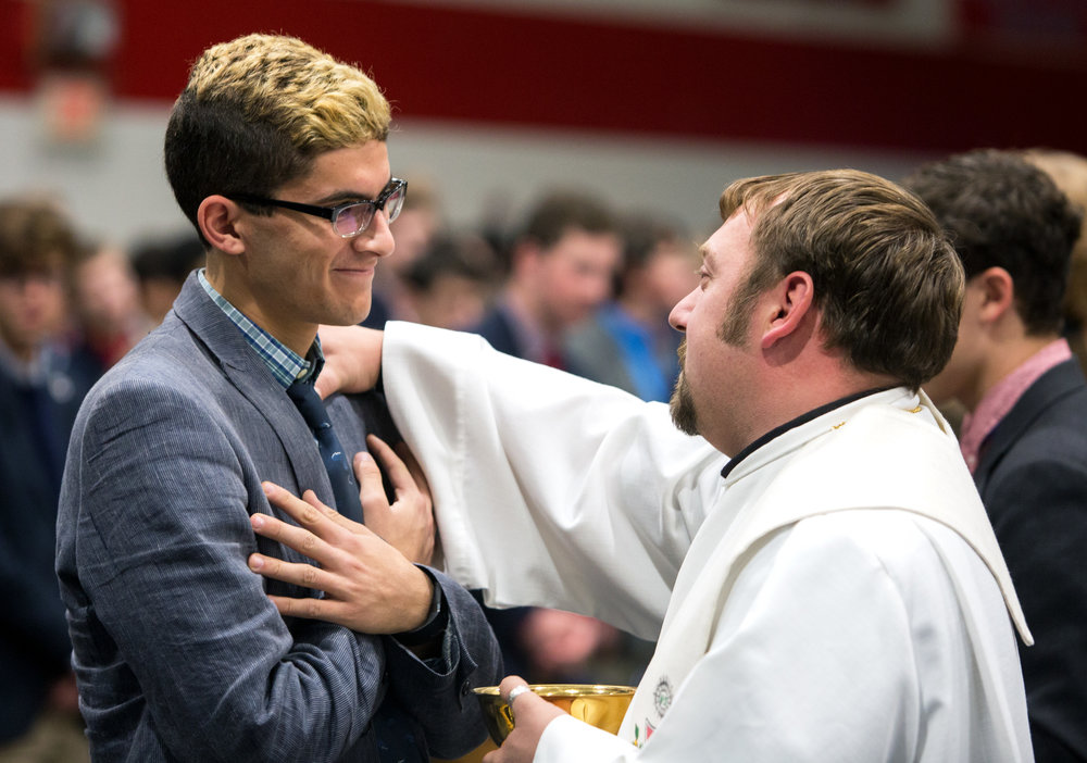 St. Francis De Sales senior Jadd Awad, left, receives a blessing from Father Rudi Schwarzkopf, right, during an all school mass to bless the Thanksgiving baskets to be delivered to community members in need at St. Francis De Sales School in Toledo, Oh. on Tuesday, Nov. 22, 2016.
