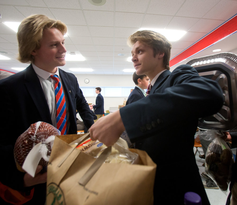 Francis De Sales students Ben Schlachter, left, Will DuPuis, right, grab the bags of non-perishable foods to be delivered to community members in need over the Thanksgiving holiday weekend at St. Francis De Sales School in Toledo, Oh. on Tuesday, Nov. 22, 2016.