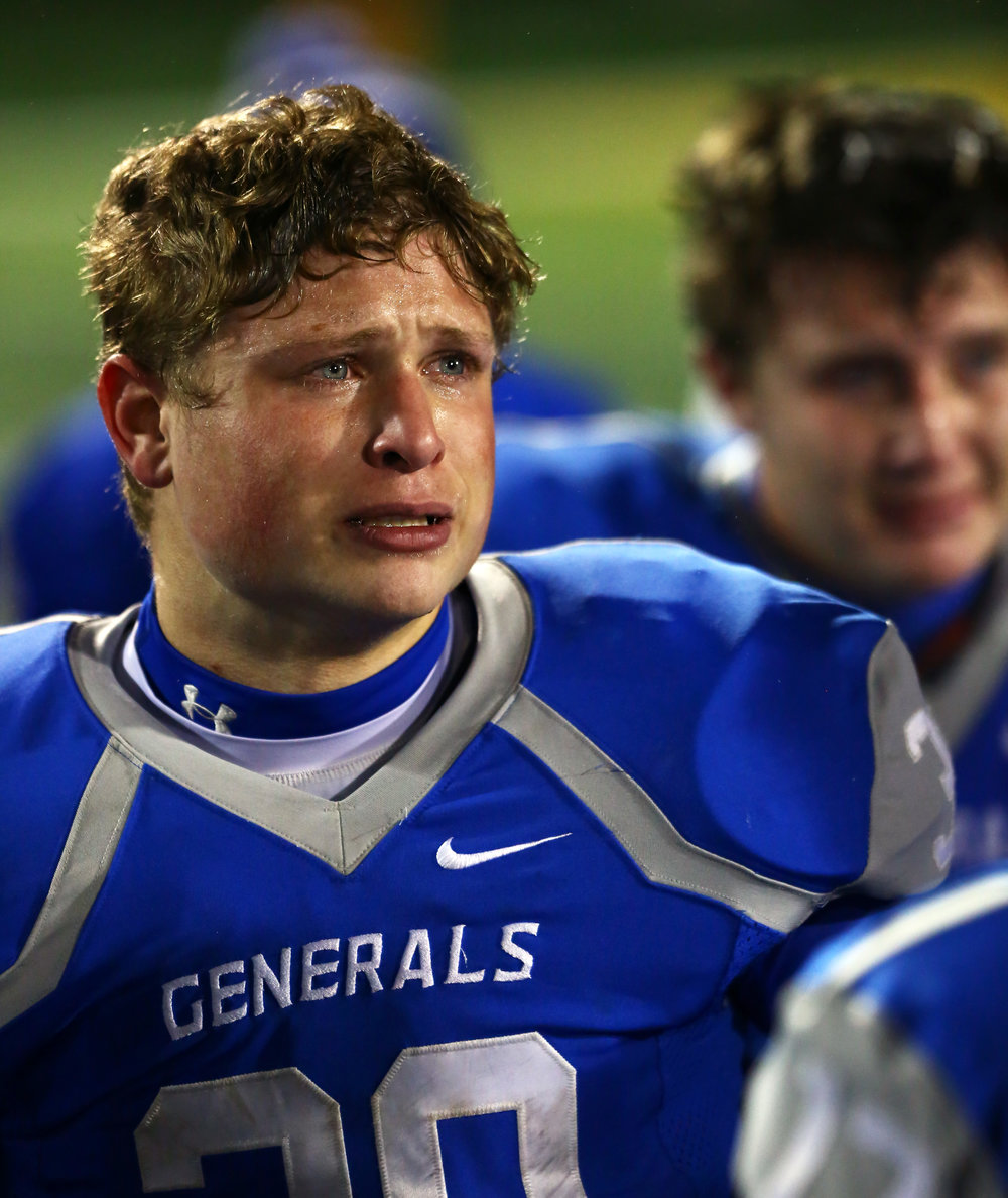 Anthony Wayne High School linebacker Robby Whitman tries to hold back tears while listening to head coach Andy Brungard's post game speech after their 35-0 loss to La Salle High School in the Div. II state semi-final football game at Sidney High School in Sidney, Oh. on Friday, Nov. 25, 2016.