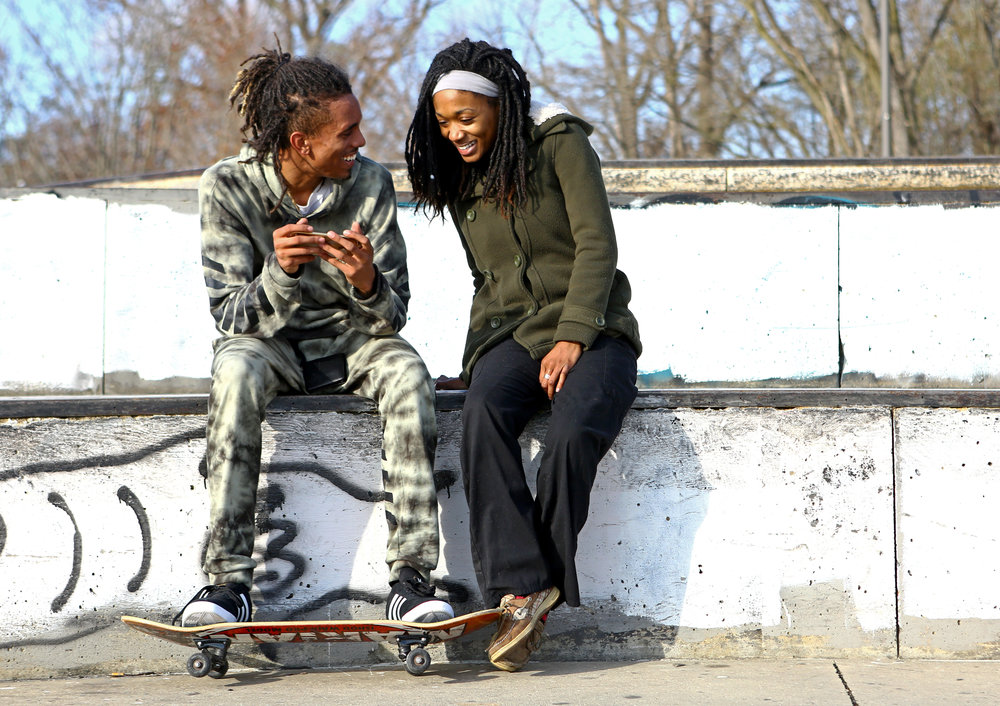 Donte Schmidt, left, takes a break from skateboarding at the Highland Park skate park to sit with his girlfriend, Naomi Grays, and watch video clips that she recorded of the session in Toledo, Oh. on Tuesday, Nov. 29, 2016.