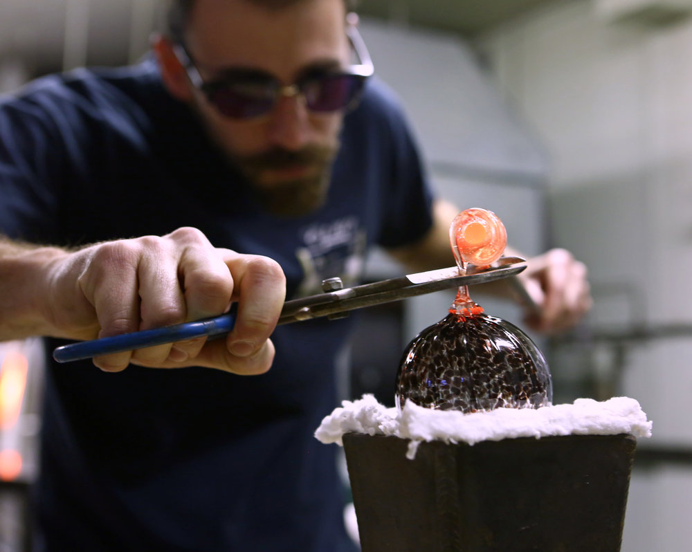 Production assistant Brien Strancar snips off molten glass to add a stem hook to a glass bulb ornament at Firenation Glass Studio in Holland, Oh. on Thursday, Dec. 1, 2016.