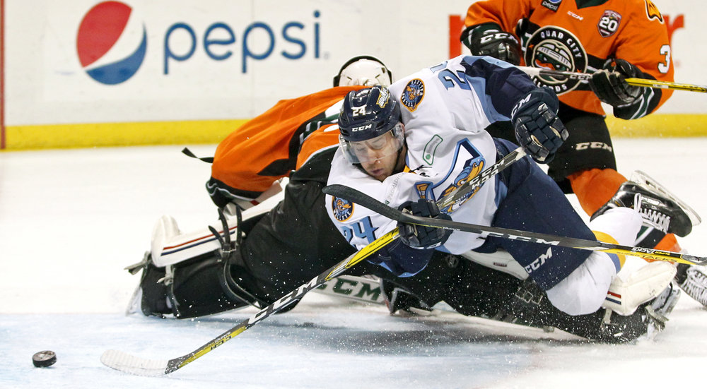 Toledo Walleye forward Tylor Spink (24) dives around Quad City Mallards goalie C.J. Motte as he slides the puck into the net, scoring the first goal of the ECHL hockey game at the Huntington Center on Saturday, Dec. 3, 2016.
