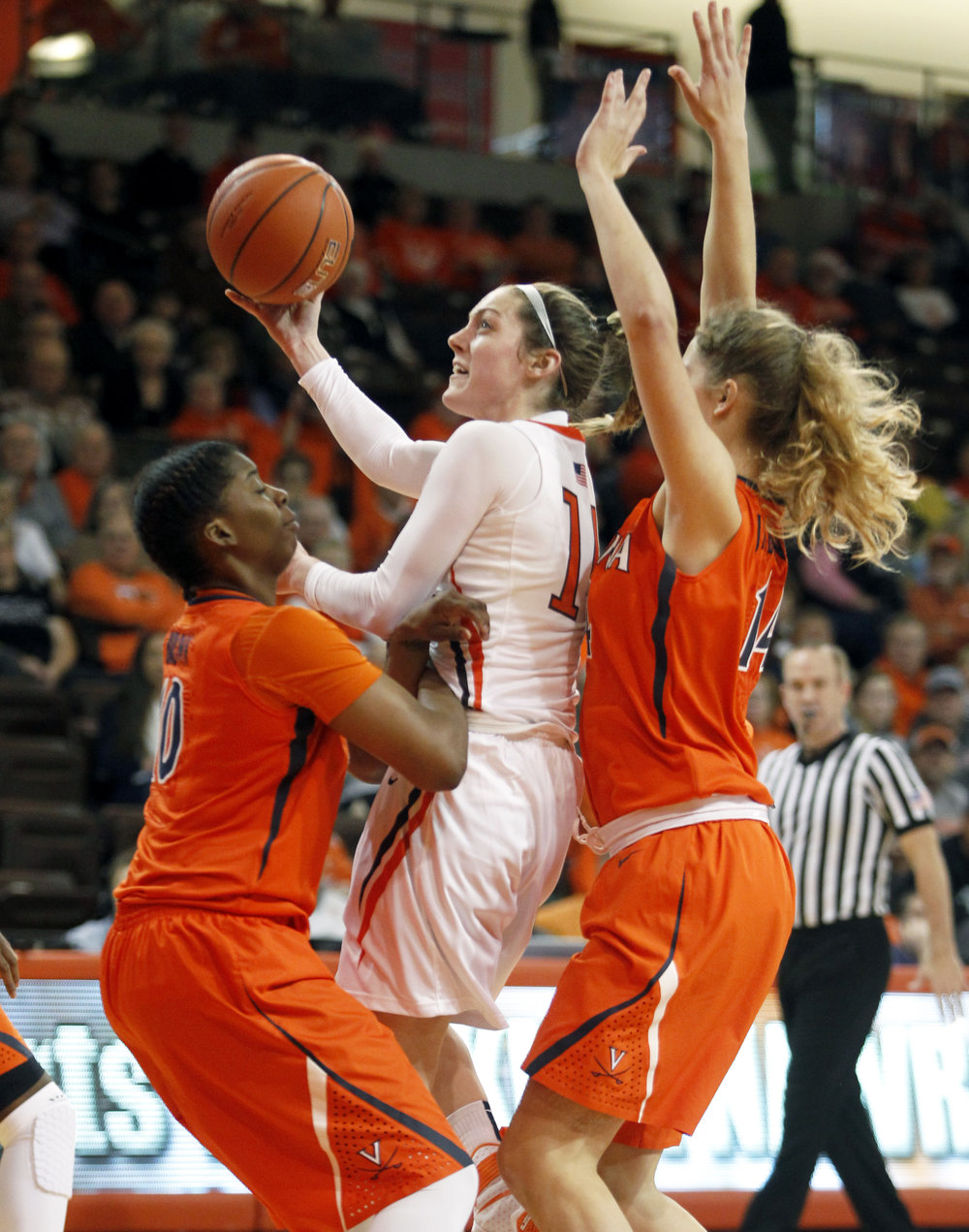BGSU guard Rachel Myers (11) jumps for a layup while under heavy coverage from University of Virginia guard J'Kyra Brown (10) and forward Lisa Jablonowski (14) during the women's basketball game at the Stroh Center in Bowling Green, Oh. on Sunday, Dec. 4, 2016.