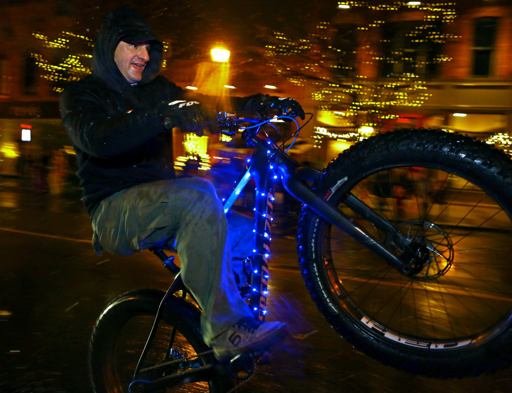 Don DiBartalomer of the Spokes Life bike shop holds a manual on his Specialized mountain fat tire bike while riding in the Miracle on Main Street holiday lights parade and tree lighting in downtown Sylvania, Oh. on Sunday, Dec. 4, 2016.