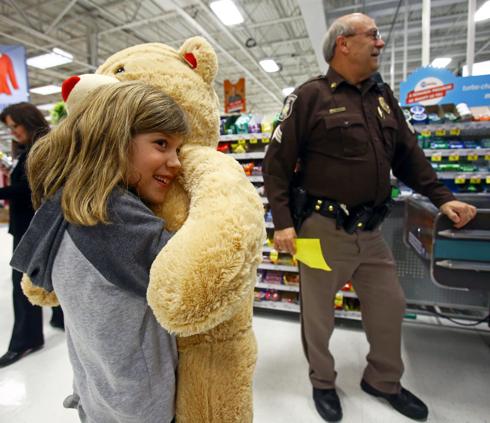 Hailey Twigg, 7, of Sylvania, left, hugs the oversized teddy bear she picked out after finding out more money available to spend while shopping with Sylvania Township Police Sgt. Clarence Whalen during Shop with Hero at the W. Central Ave. Meijer store in Toledo, Oh. on Monday, Dec. 5, 2016.