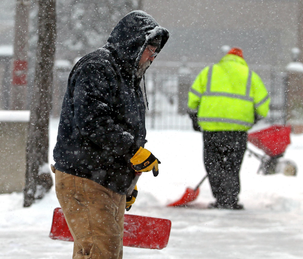 TARTA mechanics and maintenance workers Tim Swisher, left, and Ken Brockman work on clearing the snow from the bus stop on the corner of Jackson St. and Superior St. in downtown Toledo, Oh. on Sunday, Dec. 11, 2016.