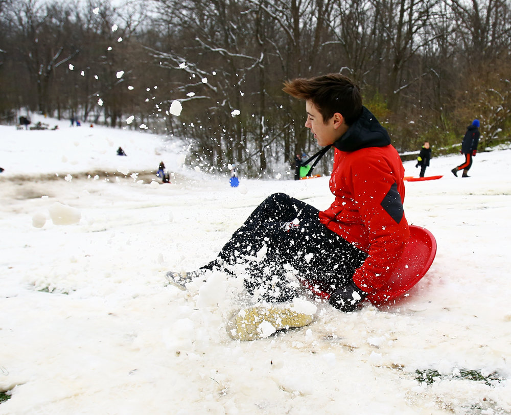 Cardinal Stritch High School student Paul Latz of Toledo jumps on to his saucer sled at the sledding hill in Pearson Metropark in Oregon, Oh. during a snow day on Monday, Dec. 12, 2016.
