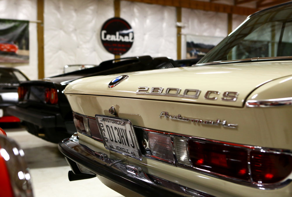 A BMW 2800cs Automatic sits next to a Ferrari 308 GTB along with the rest of Central Classic Cars' extensive inventory.