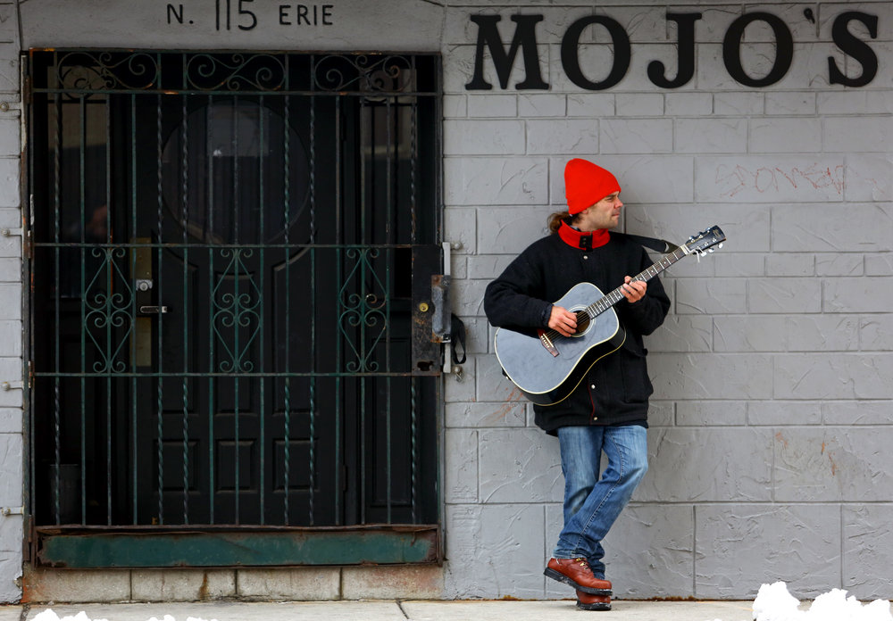 """Andrew Schively of Toledo plays his guitar outside of Mojo's on Erie Street in downtown Toledo, Oh. on Tuesday, Dec. 13, 2016. Schively normally does what he calls a """"walk and jam"""" because he likes to play his guitar outside of his apartment, but today he stopped at Mojo's to visit a friend who works at the bar."""