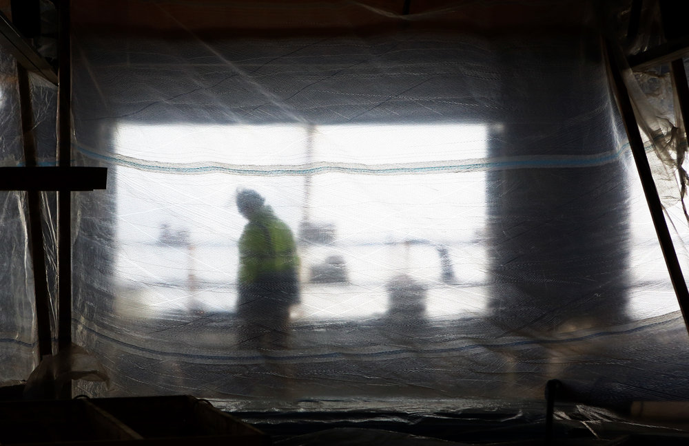 A Rudolph Libbe contractor works in a sectioned off portion of the top floor of the old steam plant building to shield from the wind off the Maumee River while working on the renovation project for ProMedica's new downtown headquarters during the frigid weather on Wednesday Dec. 14, 2016.