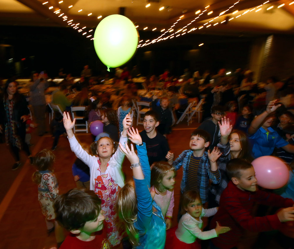 Rebeca Weingarten, 7, of Sylvania reaches for a balloon on the dance floor during the Temple Shomer Emunim's Hanukkah celebration at the temple in Sylvania, Oh. on Sunday, Dec. 18, 2016.