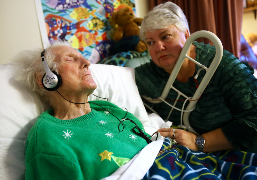 Nancy Shrider of Bowling Green, right, watches over her mother Donnagene Shrider as she listens to a mix of Christmas music on an iPod Shuffle as part of the Music and Memory program at Bowling Green Manor nursing home in Bowling Green, Oh. on Monday, Dec. 19, 2016.