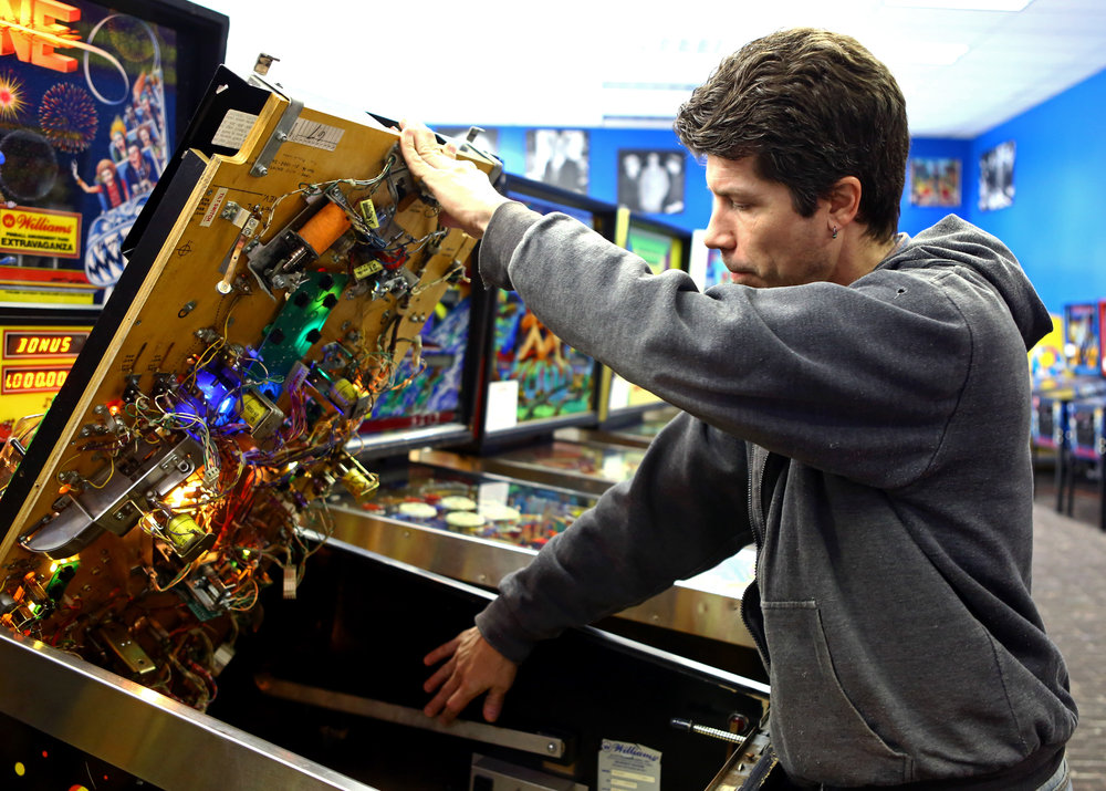 Lead tech Ron Coon of Toledo opens up one of the restored pinball machine at Dr. Scott's Pinball store in Maumee, Oh, Friday, Dec. 23, 2016.