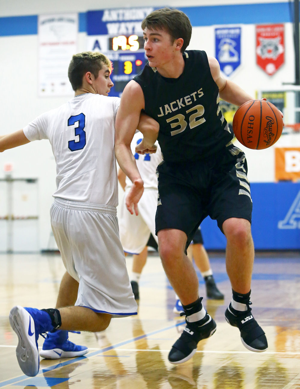 Anthony Wayne High School guard Connor Trost (3) throws an elbow into the side of Perrysburg High School forward Zach Pohlman (32) as he makes his way to the net during the varsity boy's basketball game at Anthony Wayne High School in Whitehouse, Oh, Friday, Dec. 23, 2016. Perrysburg won the game 65-45.